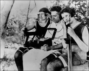 Drei Menschen sitzen auf einer Schaukel und hören Radio